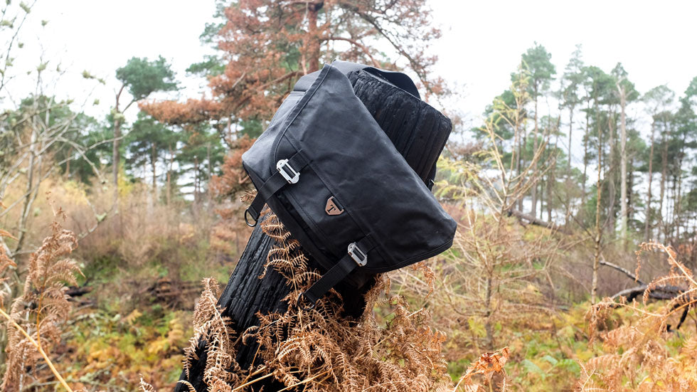 The Bairn messenger bag hangs off the stump of a tree in Balmaha, Scotland