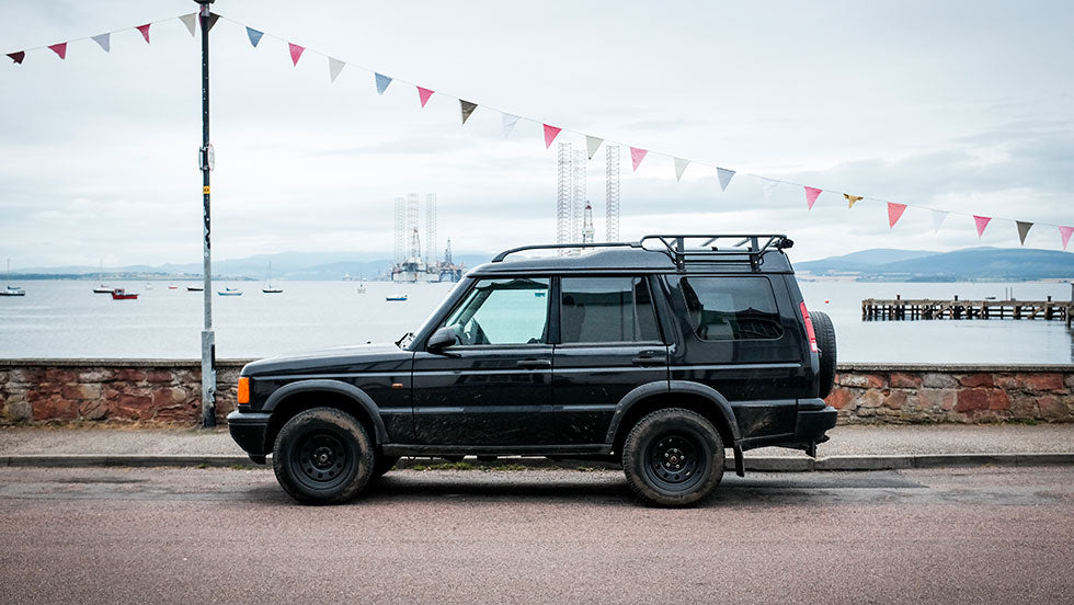 An old 4x4 land rover sits infront of multi coloured bunting