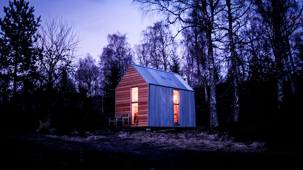 A Bothy cabin sits at dusk in the middle of a forested area with it's light illuminating the inside