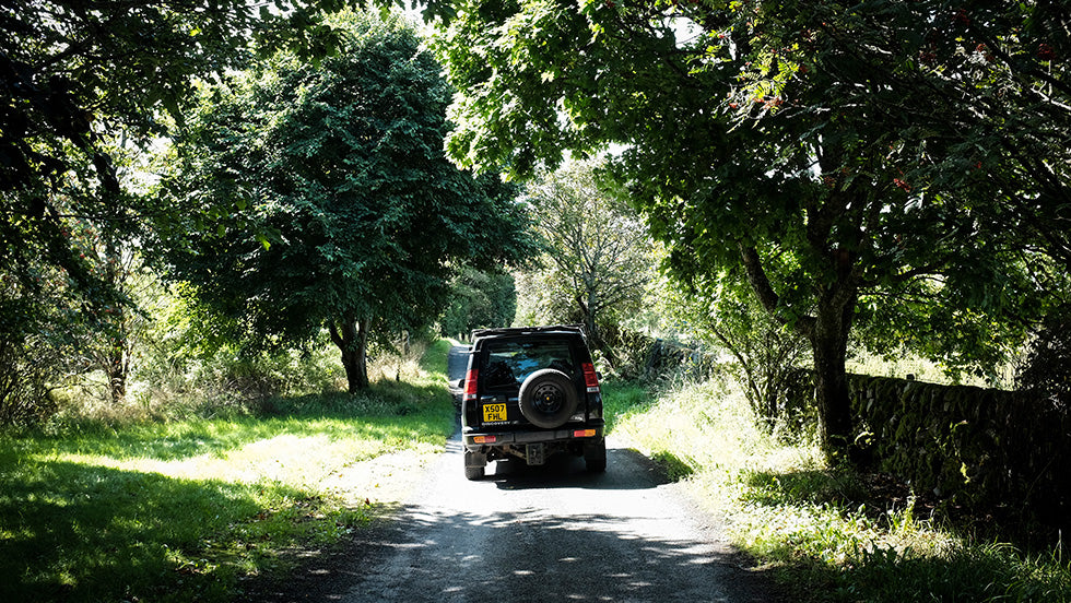 A black landrover is driving down a path lined with trees on either side on the east coast of Scotland