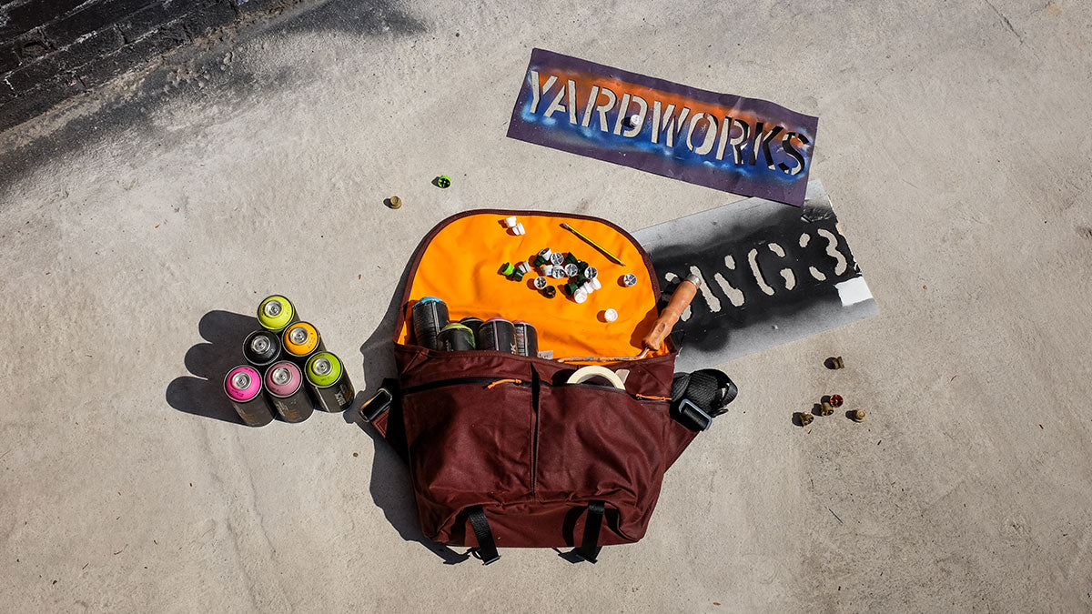 A Wee Lug waxed canvas messenger bag surrounded by graffiti equipment