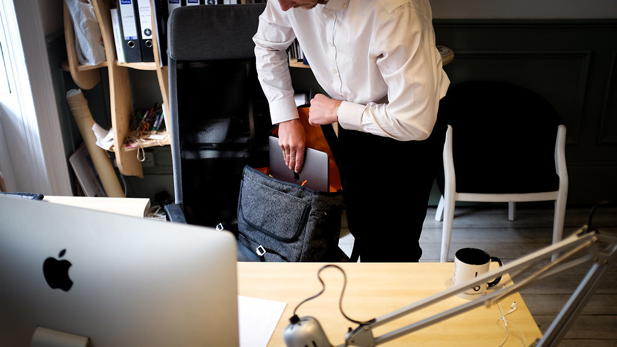 "a man loading a 13"" laptop into a bannoch messenger bag while on an overnight business trip."