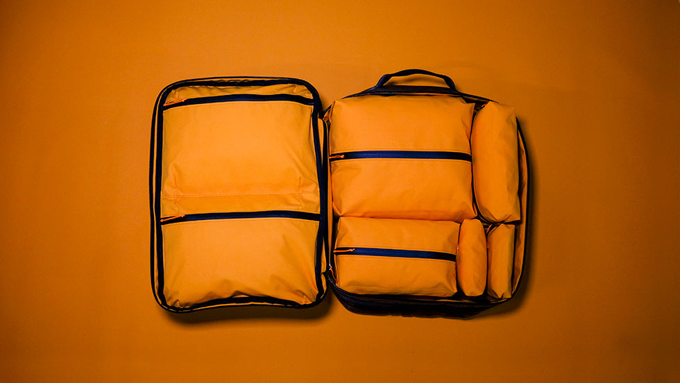 a storr hand luggage backpack filled with foulden packing cubes.
