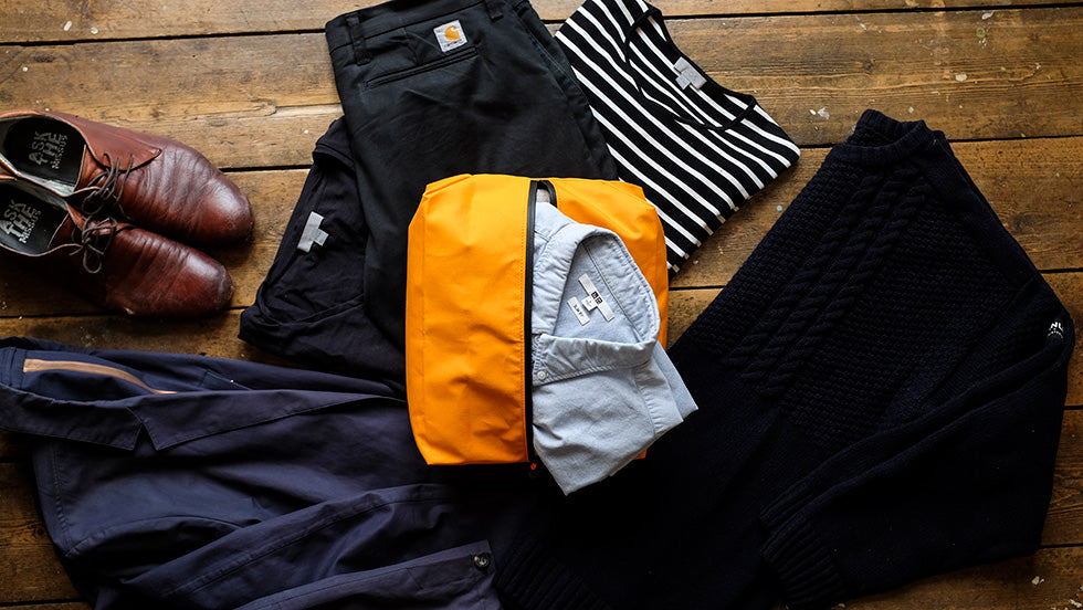 Clothes are laid flat on the floor surrounding an orange Foulden packing cube by Trakke