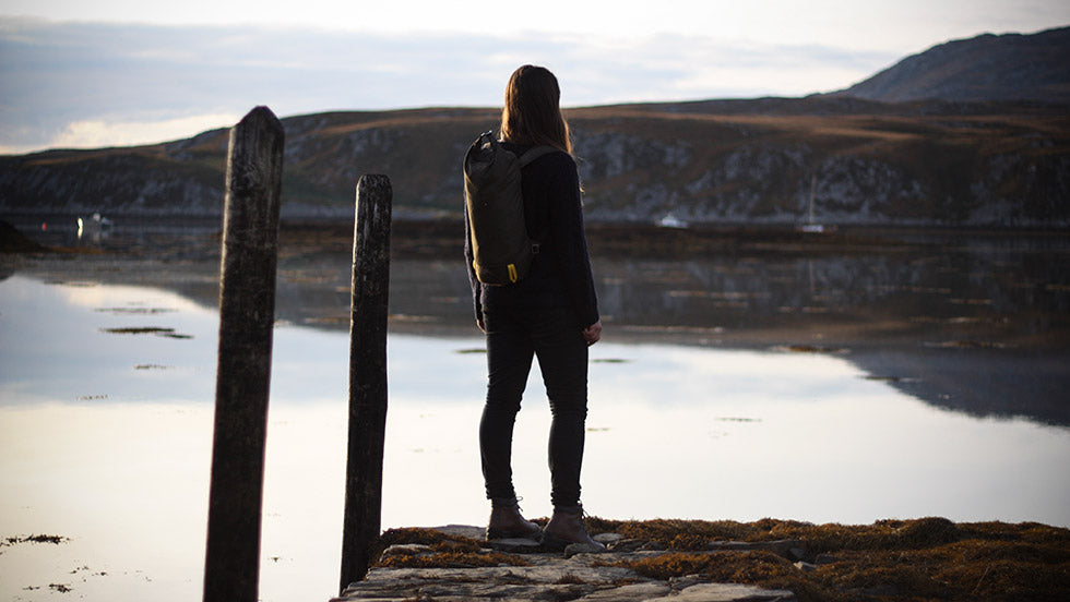 A women stands on a pier on the isle of jura looking outwards wearing her Trakke bag