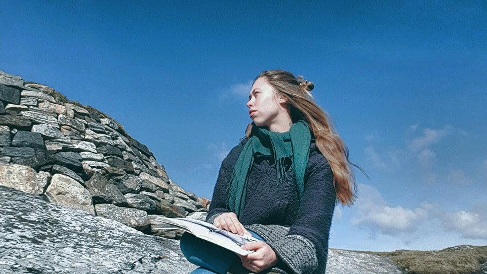 Scottish landscape artist Ellis O'Connor sits on a cliff side and looks out holding a canvas and pencil