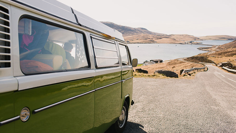 a vw van sits on a winding road in Uist on the Outer Hebrides