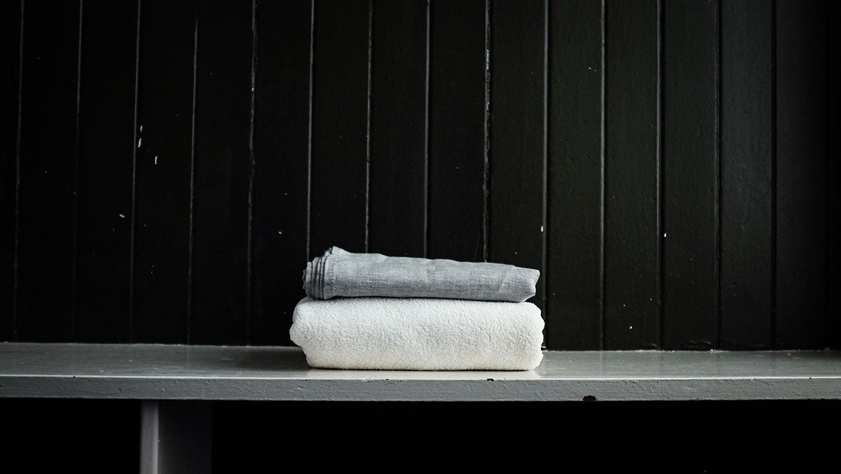 a linen travel towel alongside a regular cotton towel for comparison.
