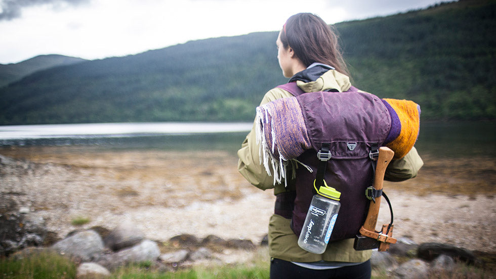 A women stands by a shore with her Assynt 28 and various items attached to the back with lashing straps