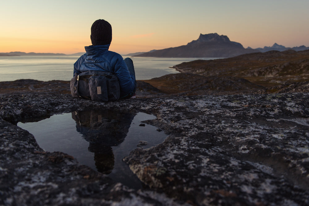 a man reclined leaning against a backpack watching the sunset over a fjord and mountain
