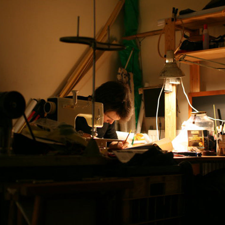 A man works on a canvas bag in a bed room and on a sewing machine