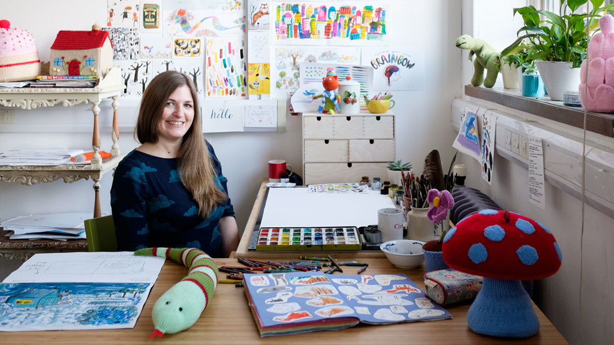 Emily mackenize at her desk surrounded by prints