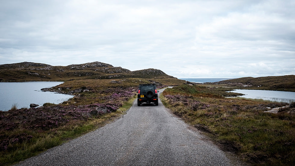 a land rover discovery driving down a single track road in scotland