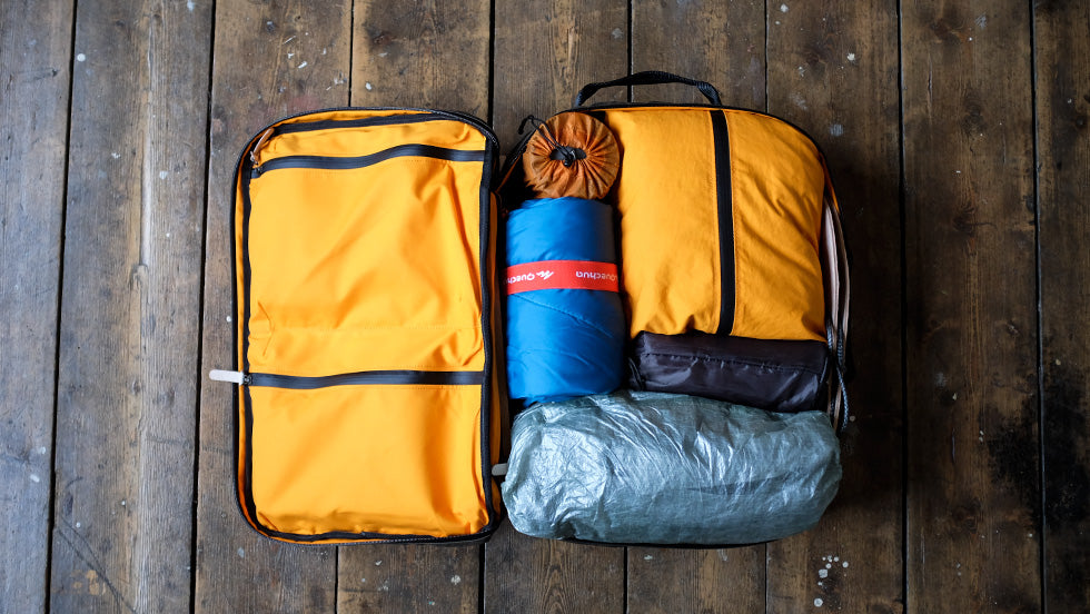 the Storry Carry On Handluggage Backpack is opened up to show neatly packed travel accessories in various colours