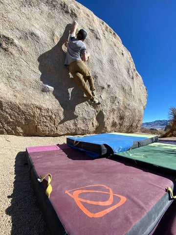 Climber on the Tut Boulder in the Buttermilks, using Asana Crash Pads.