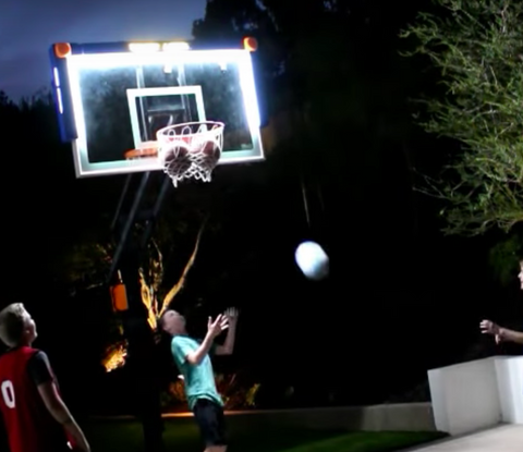 kids playing on basketball hoop with lights