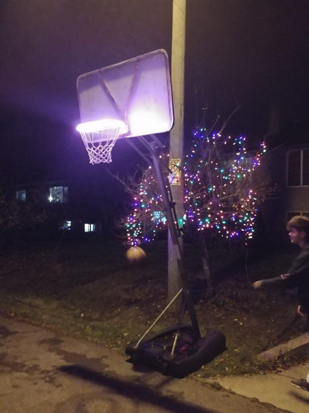 hooplight on basketball hoop with christmas lights in background