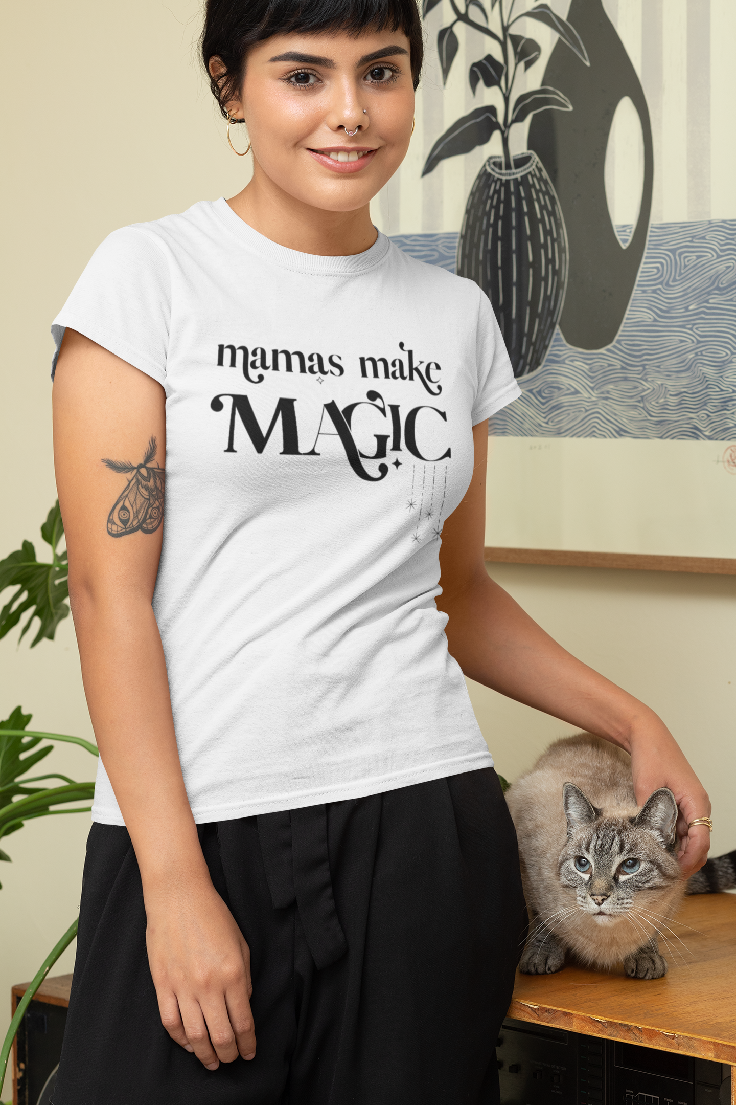Smiling woman wearing a white tee shirt printed with the words mamas make MAGIC in black