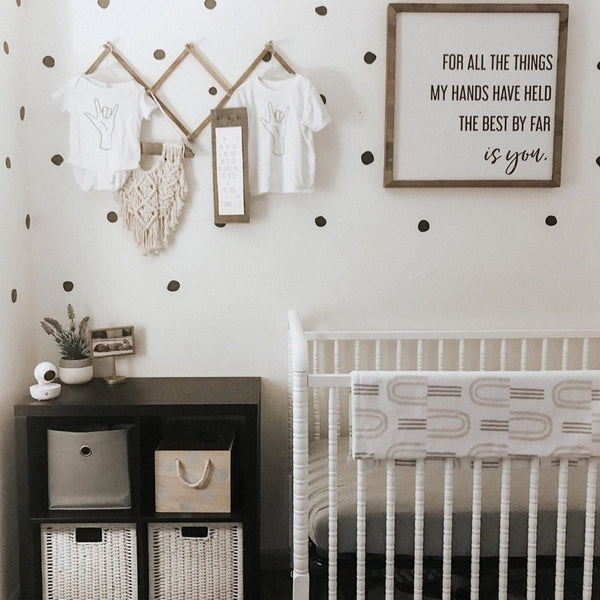 baby nursery with hanging white bodysuits printed with the ASL sign for I love you