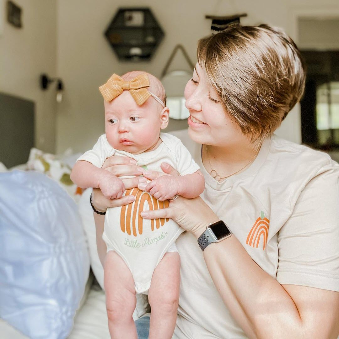mother and infant daughter wearing matching shirts printed with orange colored rainbows in the shape of pumpkins.