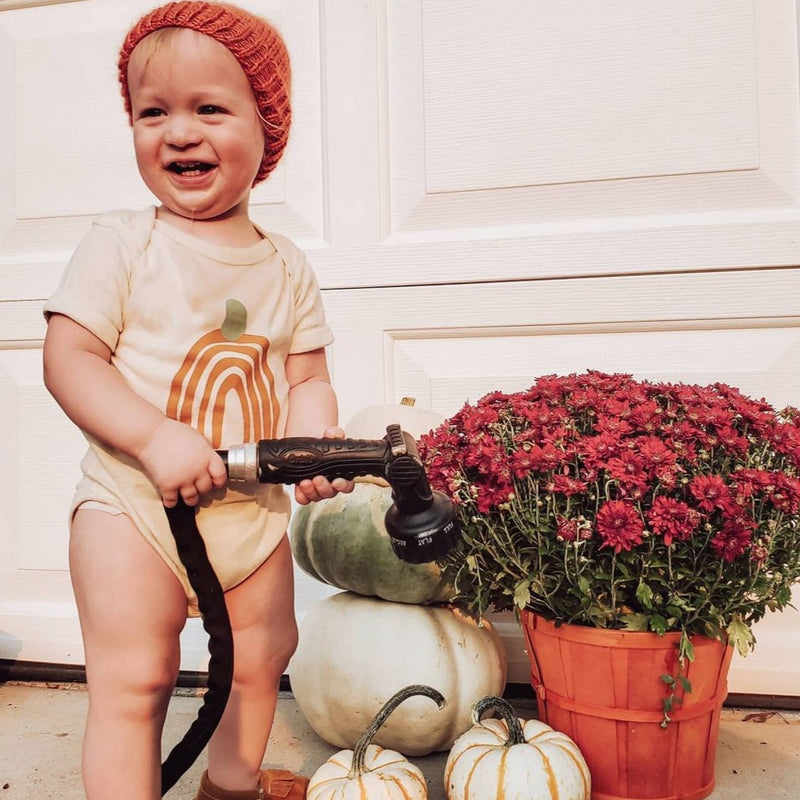 baby boy watering flowers wearing a bodysuit printed with an orange rainbow in the shape of a pumpkin.