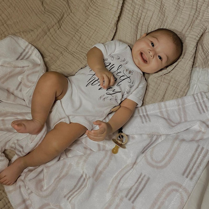 smiling baby laying down, wearing a bodysuit printed with the words sweet as honey with a minky blanket printed with gray colored rainbow shapes.