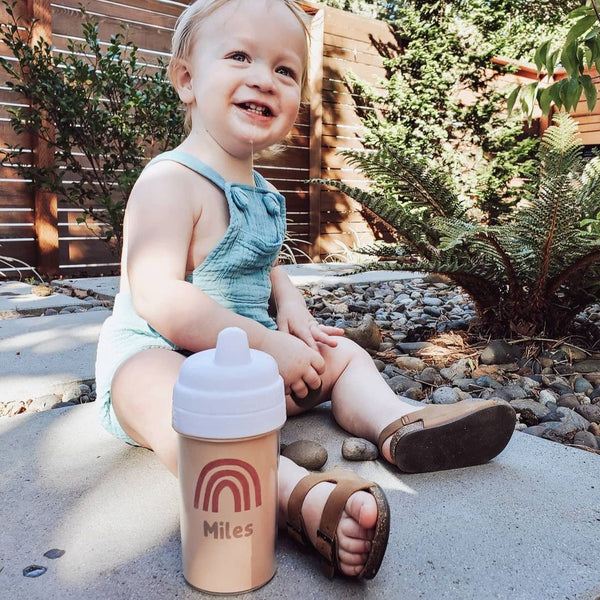 smiling baby boy sitting outside on the ground, wearing blue overall shorts with a suppy cup printed with a rust colored rainbow and the name Miles