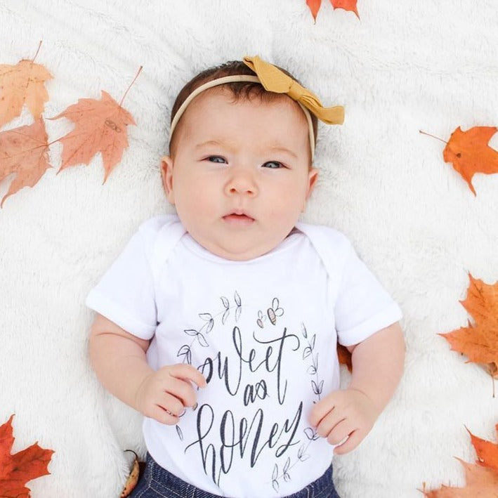 baby girl laying down, surrounded by fall leaves, wearing a bodysuit printed with the words sweet as honey