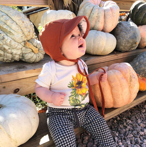 Baby sitting on a wooden bench surrounded by pumpkins and gourds, wearing a rust colored bonnet, a bodysuit printed with a sunflower, and black and white checkered pants