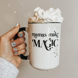 hand holding a mug overflowing with whipped cream, the mug has a black handle and is printed with the words mamas make magic