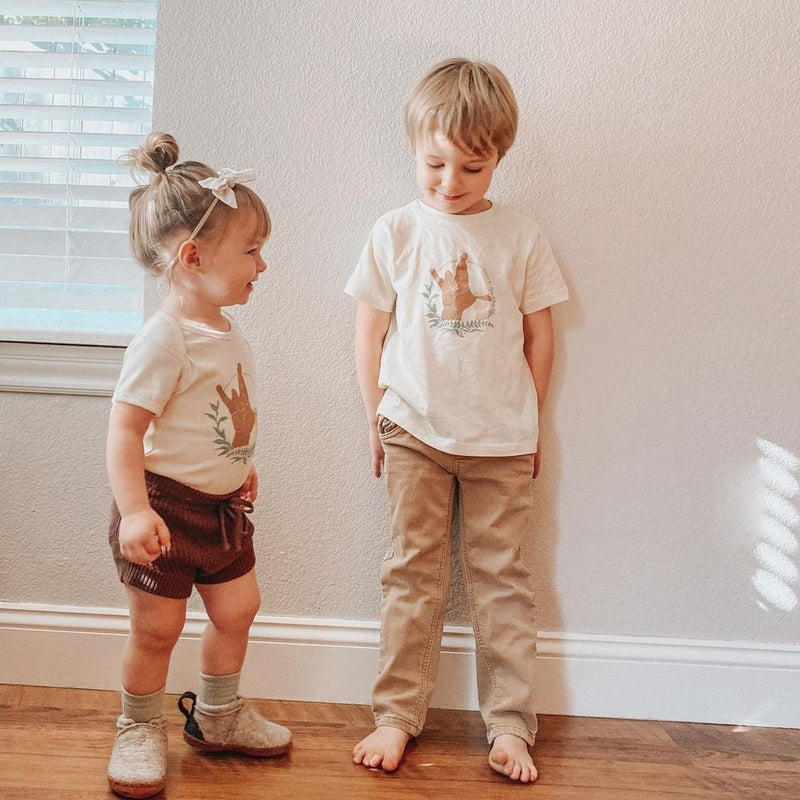 Siblings wearing matching shirts printed with the America Sign Language (ASL) sign for I really love you