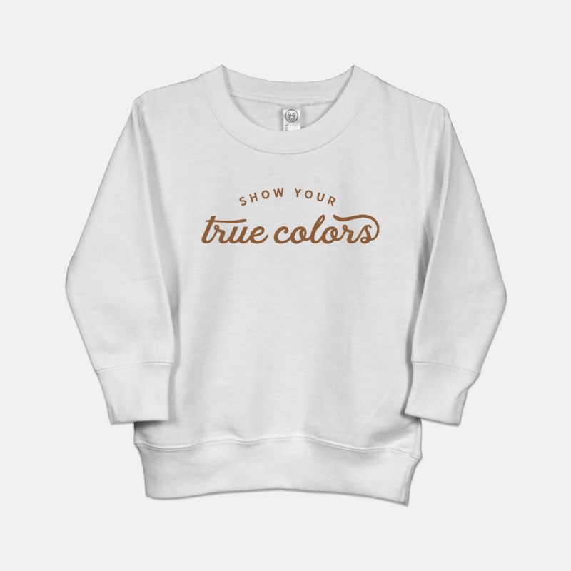 White toddler sweatshirt printed with the words show your true colors.
