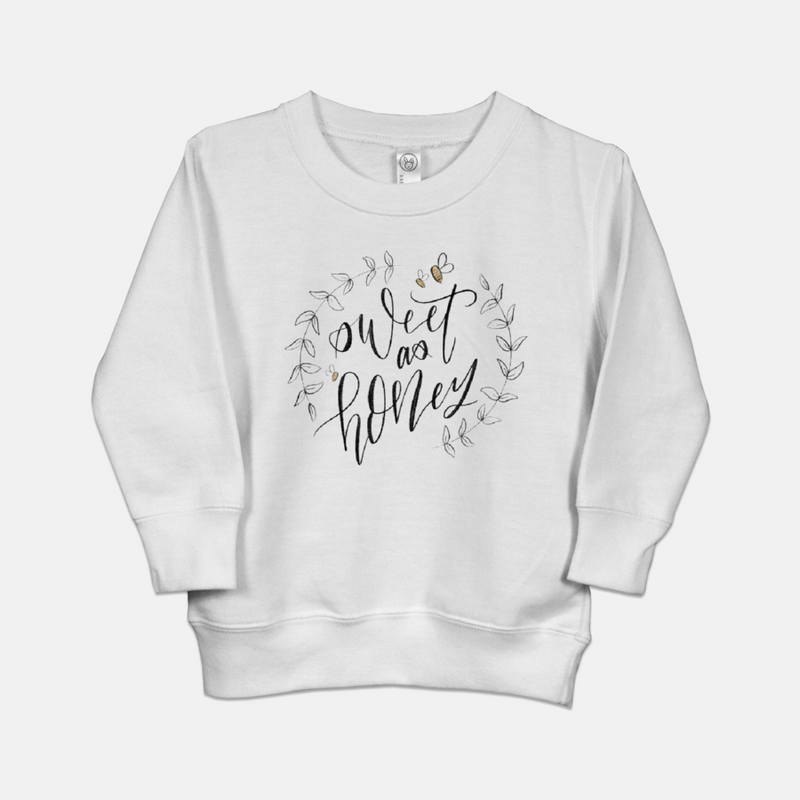 White toddler sweatshirt printed with a hand drawn wreath of leaves, three honeybees, and the words sweet as honey in cursive.