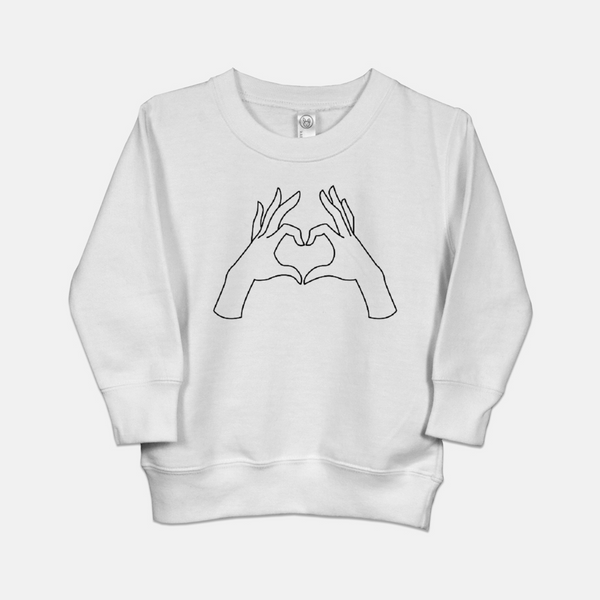 White toddler sweatshirt printed with the outline of two hands forming the shape of a heart.