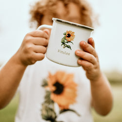 child holding a white enamel mug printed with a sunflower and the name Kinslee