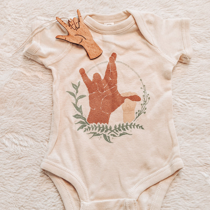 American Sign Language (ASL) printed bodysuit with the sign for I really love you and a wooden ornament with the sign for I love you