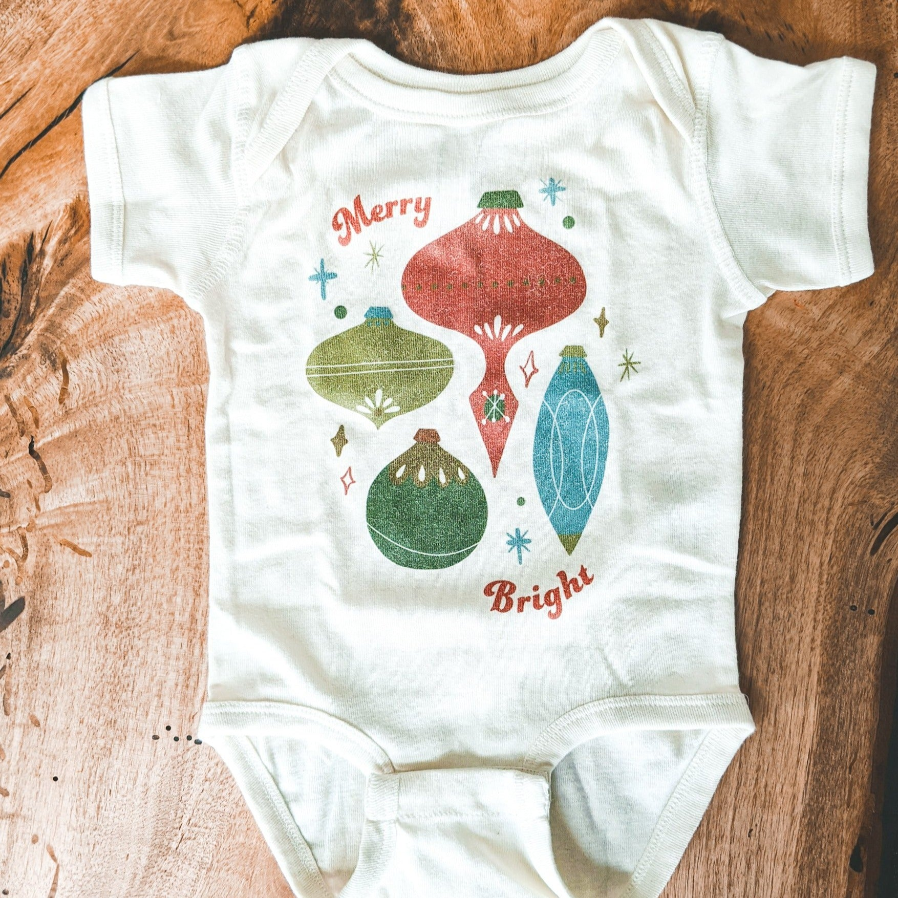 baby Christmas onesie printed with vintage ornament illustrations and the words Merry Bright