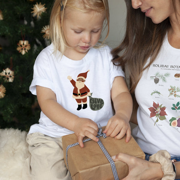 toddler girl opening a gift, she's wearing a white tee shirt printed with a vintage Santa Claus illustration