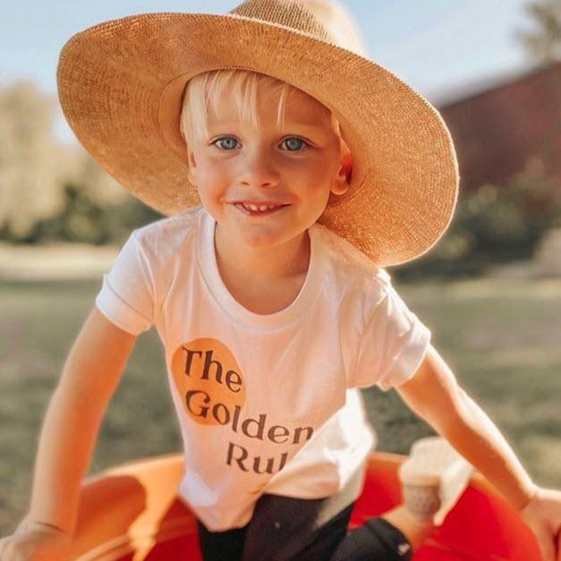 smiling  toddler boy wearing a large straw hat and a white tee shirt printed with a yellow circle and the words The golden Rule