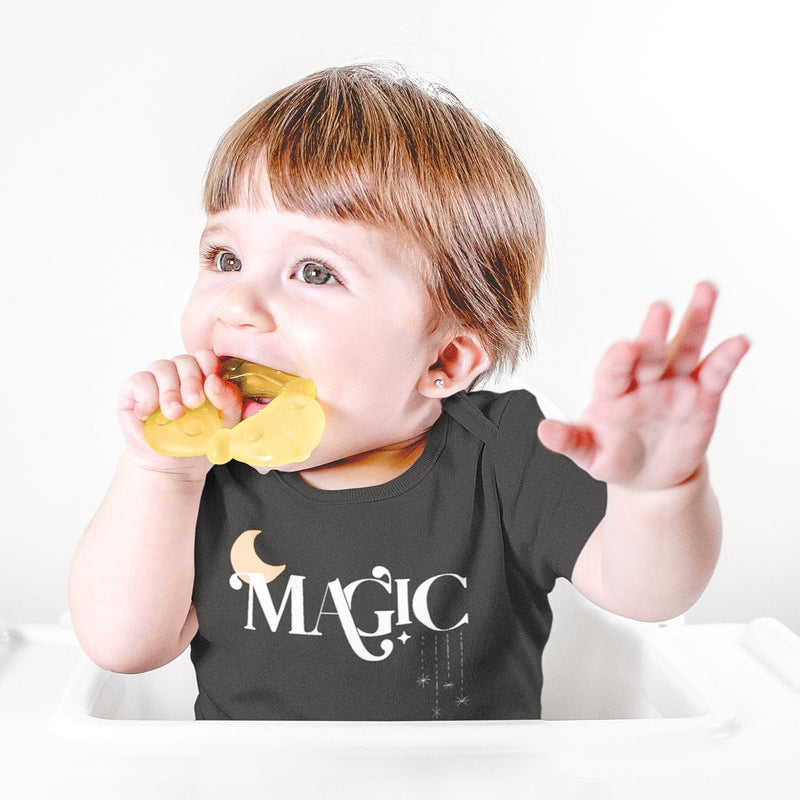 baby wearing a black bodysuit printed with the word magic
