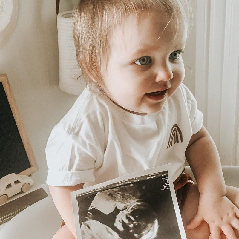 toddler with an ultrasound photo wearing a white tee shirt printed with a rust colored rainbow