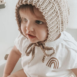 toddler girl wearing a tee shirt printed with a small rust colored rainbow in the top right corner, and wearing a knit bonnet