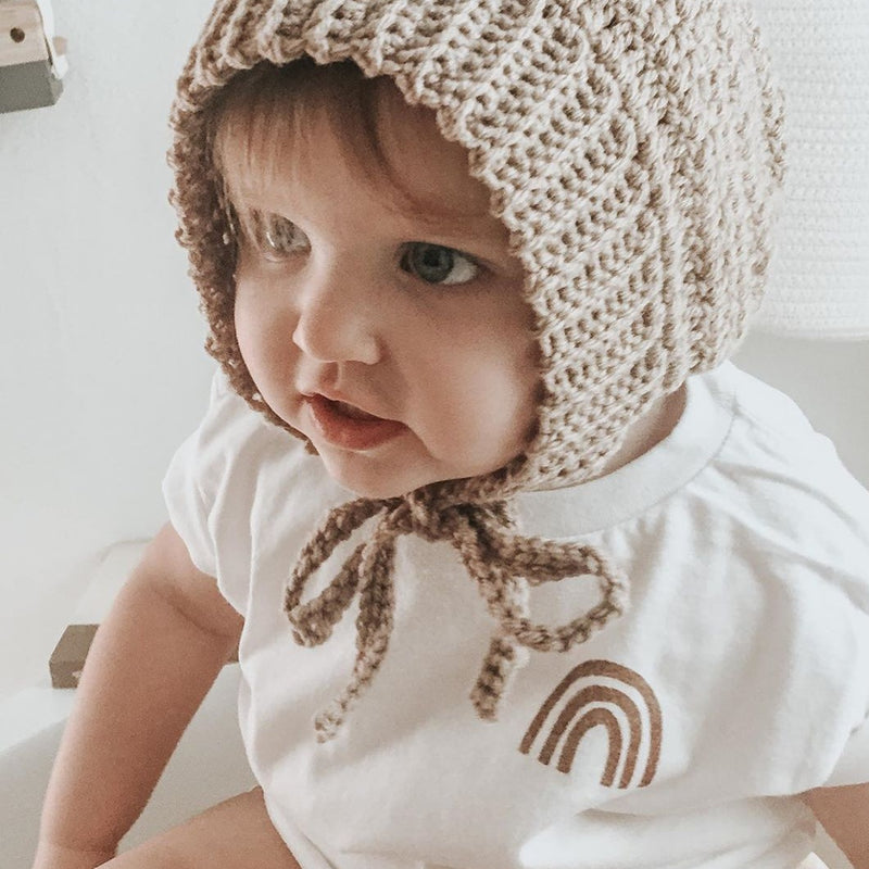 toddler wearing a tan colored knit bonnet and white tee shirt printed with a rust colored rainbow