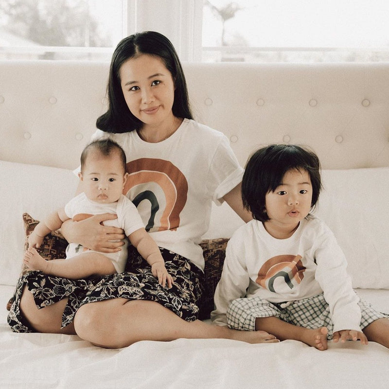 mother sitting with her toddler and baby, all  are wearing matching earthy rainbow printed shirts