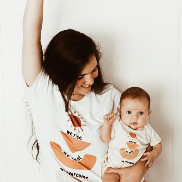 mom holding her baby, both are wearing matching shirts printed with a sun, abstract shapes, and the words we rise, we heal, we overcome