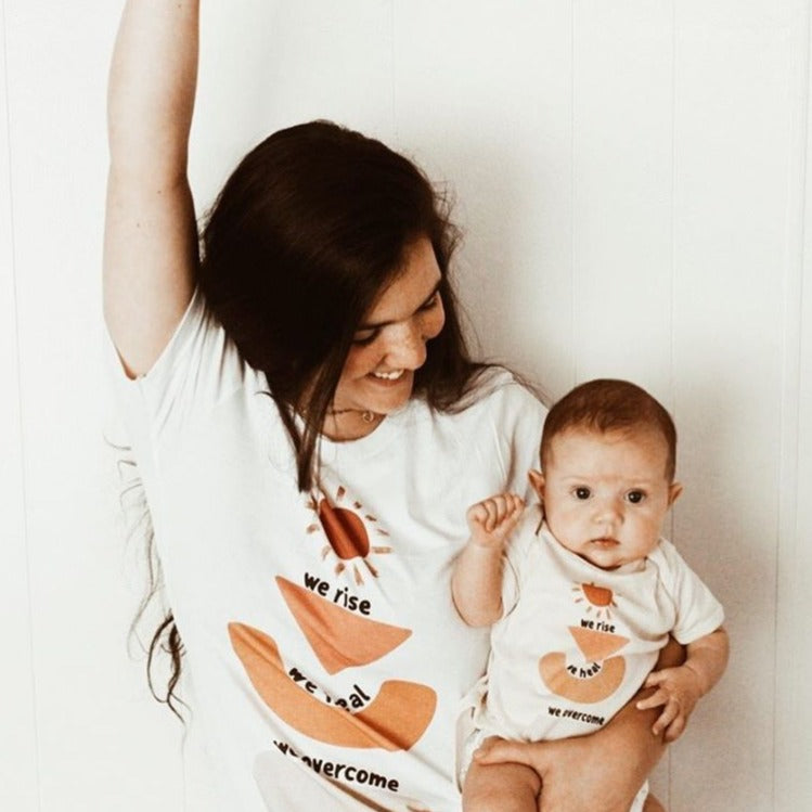 smiling mom holding her baby who is a bodysuit printed with a sun, abstract shapes, and the words we rise, we heal, we overcome. Mom is wearing a matching shirt and both have one hand in the air