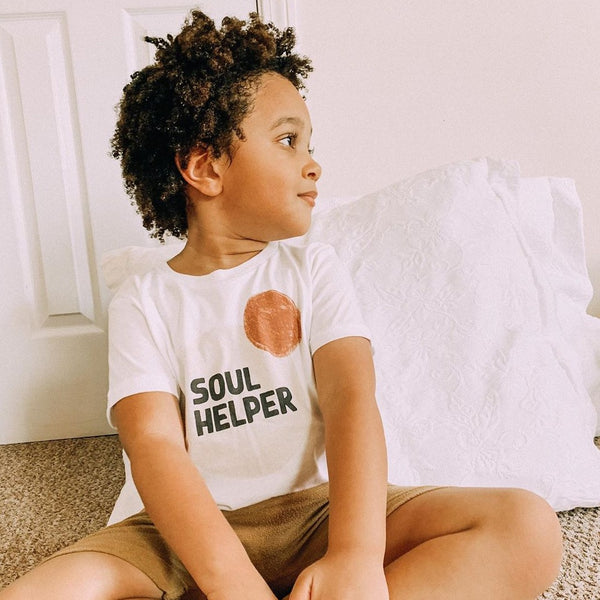 Smiling toddler boy wearing a white tee shirt printed with abstract, neutral colored circles and the words Soul Helper