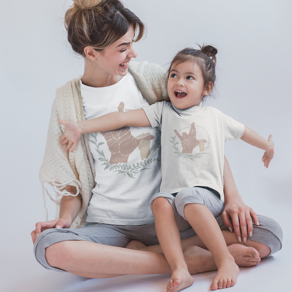 mother and daughter sitting on a floor, wearing matching tee shirts printed with American Sign Language (ASL) unisex adult tee shirt printed with the phrase I really love you.
