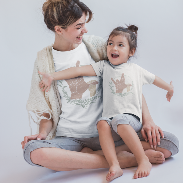 Mother and daughter sitting on the floor, both are wearing American sign language shirts printed with the sign for I really love you being formed by an adult hand with a baby hand holding the thumb