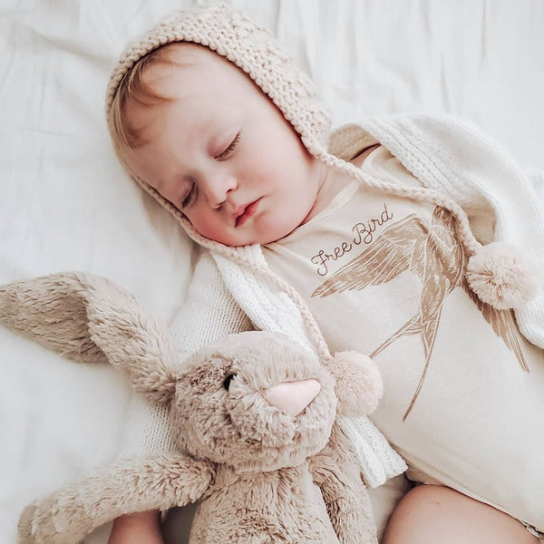 sleeping baby wearing a cream colored knit bonnet, white sweater, and a bodysuit printed with a flying sparrow and the words free bird. There is a stuffed beige colored rabbit lying next to him.